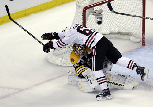 Chicago Blackhawks center Andrew Shaw (65) collides with Boston Bruins goalie Tuukka Rask, underneath, of Finland,during the first period in Game 3 of the NHL hockey Stanley Cup Finals in Boston, Monday, June 17, 2013. (AP Photo/Charles Krupa)