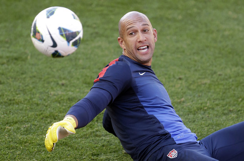 U.S. national soccer team goalkeeper Tim Howard, right, reaches for a ball during the start of a practice session, Monday, June 17, 2013, in Sandy, Utah. The U.S. will face Honduras on Tuesday, June 18 for a World Cup qualifier soccer match. (AP Photo/Rick Bowmer)