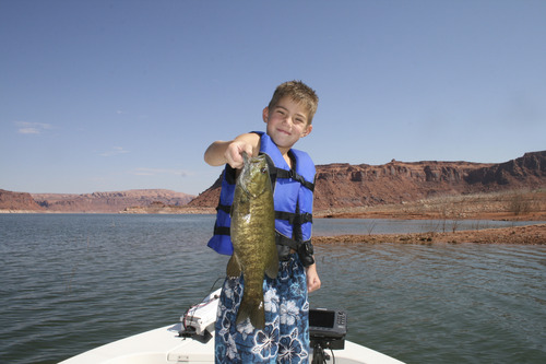Courtesy photo A youngster from Colorado proudly displays the big smallmouth he caught in Lake Powell's Good Hope Bay. Fishing for bass, walleye, crappie and stripers will continue to delight anglers through the month of November.