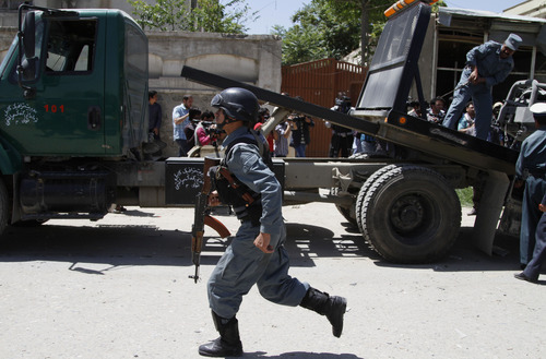 An Afghan police officer runs at the site of a blast near the Afghan Independent Human Rights Commission in Kabul, Afghanistan, Tuesday, June, 18, 2013. The large bomb exploded in the Afghan capital on Tuesday as the international military coalition hands over responsibility for fighting the Taliban insurgency to the nascent national army and police they have been training. (AP Photo/Ahmad Jamshid)