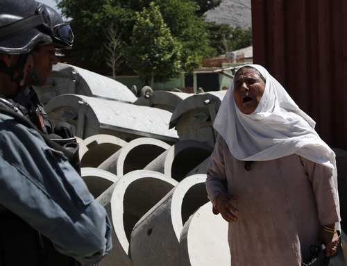 An Afghan woman cries as she talks with police at the site of a blast near the Afghan Independent Human Rights Commission in Kabul, Afghanistan, Tuesday, June, 18, 2013. The large bomb exploded in the Afghan capital on Tuesday as the international military coalition hands over responsibility for fighting the Taliban insurgency to the nascent national army and police they have been training. (AP Photo/Ahmad Jamshid)
