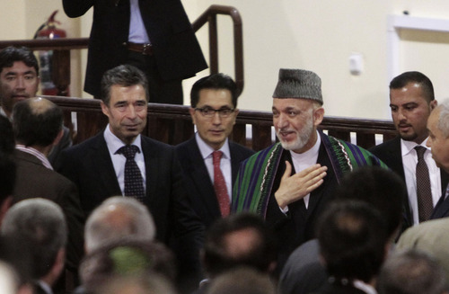 NATO Secretary-General Anders Fogh Rasmussen, center left, and Afghan President Hamid Karzai, center right, arrive at a ceremony at a military academy on the outskirts of Kabul, Afghanistan, Tuesday, June 18, 2013. Karzai announced at the ceremony that his country's armed forces are taking over the lead for security nationwide from the U.S.-led NATO coalition. (AP Photo/Rahmat Gul)