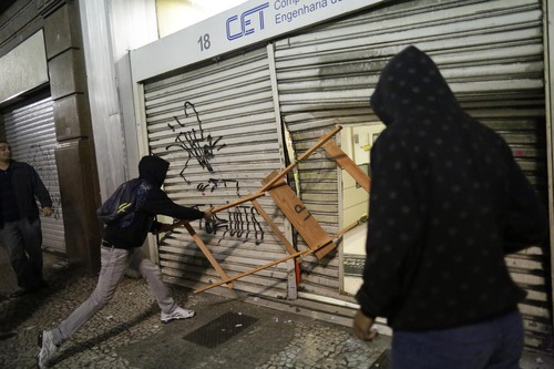 Protestors destroy a city traffic engineering center's security gate in Sao Paulo, Brazil, Tuesday, June 18, 2013. . Protests initially sparked by a 10-cent hike in bus and subway fares this month, continued Tuesday evening. Demonstrations have spread throughout Brazil and added grievances over poor government services, high taxes and corruption. (AP Photo/Nelson Antoine)
