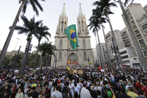 Protestors gather in front of the Metropolitan Cathedral in Sao Paulo, Brazil, Tuesday, June 18, 2013.  Some of the biggest demonstrations since the end of Brazil's 1964-85 dictatorship have broke out across this continent-sized country, uniting multitudes frustrated by poor transportation, health services, education and security despite a heavy tax burden. (AP Photo/Nelson Antoine)