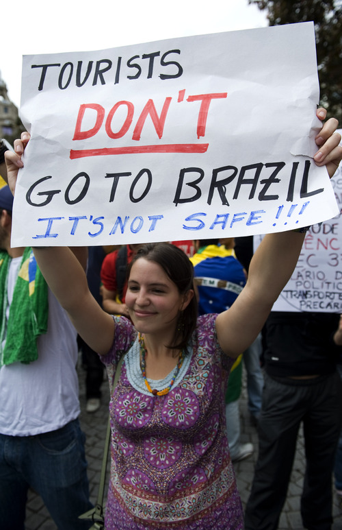 A protester holds a banner in a demonstration against the Brazilian government in Porto, Portugal, Tuesday June 18, 2013. Brazilians living and studying in Portugal took part in a protest in Lisbon and Porto condemning the current political and social situation in Brazil. (AP Photo/Paulo Duarte)