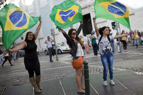 Brazilians holding their country's flag play in the updraft of a subway vent outside Lisbon's Brazilian consulate, Tuesday, June 18 2013. Hundreds of Brazilians protested in Lisbon Tuesday joining the  demonstrations of the last days across Brazil in some of the largest outpourings of frustration in decades over red tape, high prices and shoddy services.  (AP Photo/Armando Franca)