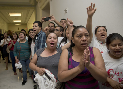 People shout out against the Strengthen and Fortify Enforcement Act in the hall outside the House Judiciary Committee hearing on Capitol Hill in Washington, Tuesday, June 18, 2013. The committee in the Republican-led House is preparing to cast its first votes on immigration this year, on a tough enforcement-focused measure that Democrats and immigrant groups are protesting loudly. (AP Photo/Carolyn Kaster)