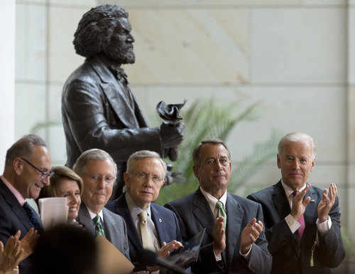 From left, Sen. Charles Schumer, D-N.Y., House Minority Leader Nancy Pelosi of Calif., Senate Minority Leader Mitch McConnell of Ky., Senate Majority Leader Harry Reid of Nev., House Speaker John Boehner of Ohio and Vice President Joe Biden applaud during a ceremony to dedicate the statue of Frederick Douglass, seen behind them, Wednesday, June 19, 2013, in the Emancipation Hall of the United States Visitor Center on Capitol Hill in Washington. The bronze statue of Douglass is by Maryland artist Steve Weitzman. (AP Photo/Carolyn Kaster)