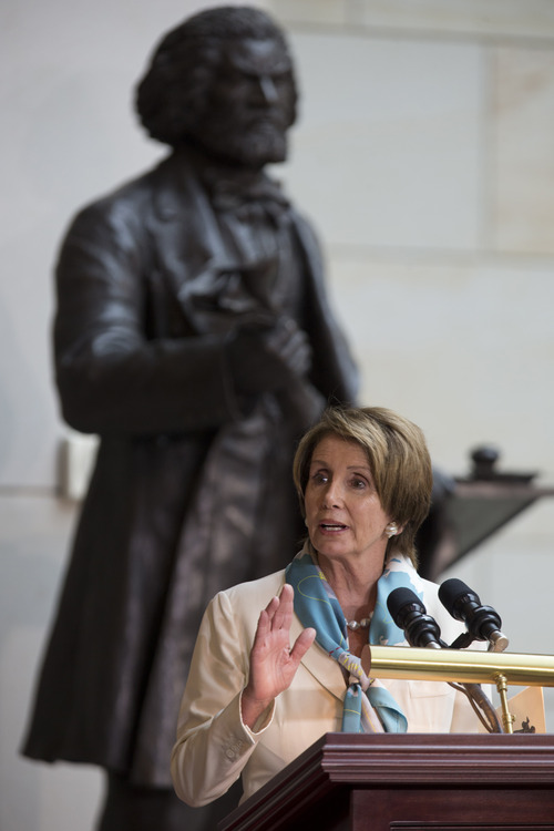 House Minority Leader Nancy Pelosi of Calif., speaks during a ceremony to dedicate the statue of Frederick Douglass, seen behind,  in the Emancipation Hall of the United States Visitor Center on Capitol Hill in Washington, Wednesday, June 19, 2013. The bronze statue of Douglass is by Maryland artist Steve Weitzman. (AP Photo/Carolyn Kaster)