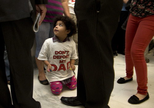 "Jackelin Alfaro, 4, in a t-shirt that reads ""Don't Deport my Dad"" sits in the hall with family members outside the House Judiciary Committee hearing on Capitol Hill in Washington, Tuesday, June 18, 2013. The committee hearing will discuss the Strengthen and Fortify Enforcement Act. The committee in the Republican-led House is preparing to cast its first votes on immigration this year, on a tough enforcement-focused measure that Democrats and immigrant groups are protesting loudly. (AP Photo/Carolyn Kaster)"