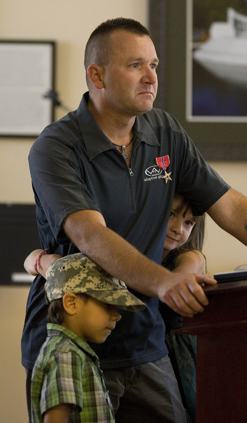 Paul Fraughton  |  The Salt Lake Tribune As he speaks to a gathering at the Veterans Hospital after receiving a Bronze Star for his service in Iraq, Sgt. Joshua Hansen is embraced Tuesday, June 18, 2013, by his children Jesse James, 6, and Trinity Rose, 9.