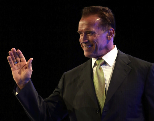 Former Governor of California Arnold Schwarzenegger waves to the audience as he arrives on stage during a Financial Education Summit in Sydney, Australia, Thursday, June 13, 2013. Schwarzenegger was a keynote speaker during the summit that toured Perth, Sydney and Melbourne, speaking about his success in body building, real estate, the film industry and politics. (AP Photo/Rob Griffith)