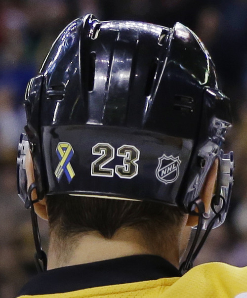 "FILE - In this April 17, 2013, file photo, Boston Bruins center Chris Kelly wears a ""Boston Strong"" decal, left, on his helmet during an NHL hockey game against the Buffalo Sabres in Boston. With their ""Boston Strong"" decals on the back of their helmets and the steady parade of Boston Marathon bombing victims honored at their games, the Bruins are hoping that a Stanley Cup victory will provide solace to those affected in the April 15 attacks. (AP Photo/Elise Amendola, File)"