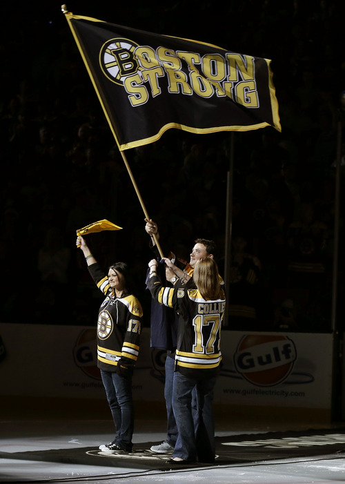 Rob Rogers, Jenn Rogers, and Jennifer Lemmerman, wave a Boston Strong banner before Game 3 of the NHL hockey Stanley Cup Finals between the Boston Bruins and the Chicago Blackhawks in Boston, Monday, June 17, 2013. The three are relatives of MIT police officer Sean Collier, killed during confrontation with suspects in the Boston Marathon bombing on April 15. (AP Photo/Elise Amendola)