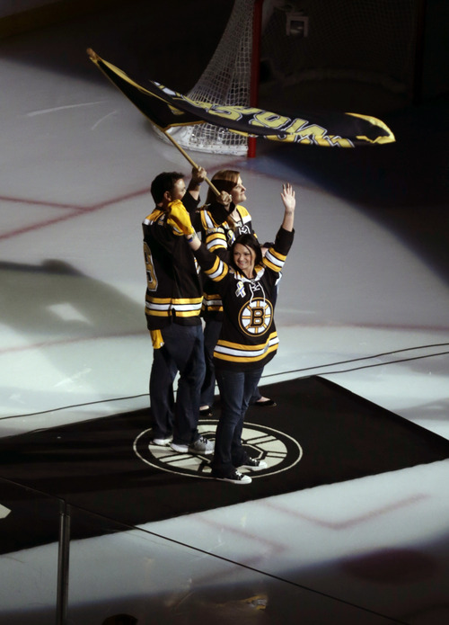 Rob Rogers, Jenn Rogers, and Jennifer Lemmerman, wave a Boston Strong banner before Game 3 of the NHL hockey Stanley Cup Finals between the Boston Bruins and the Chicago Blackhawks in Boston, Monday, June 17, 2013. The three are relatives of MIT police officer Sean Collier, killed during confrontation with suspects in the Boston Marathon bombing on April 15. (AP Photo/Charles Krupa)