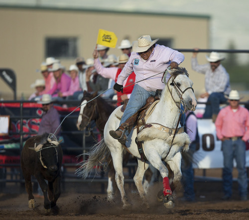 Lennie Mahler  |  The Salt Lake Tribune Cooper Larson scores a 7.99 with partner Cate Roberts to win the team roping event in the Utah High School Rodeo Championships in Heber City, Utah, Friday, June 14, 2013.