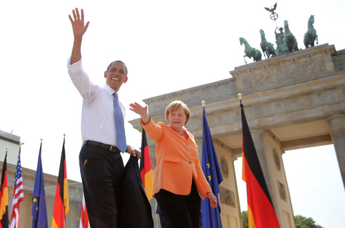 US President Barack Obama  waves to spectators before he  delivers a speech in front of the Brandenburg Gate  at Pariser Platz in Berlin, Germany,  Wednesday June 19, 2013. At right stands German chancellor Angela Merkel.   On the second day of his visit to Germany, Obama met with German President Joachim Gauck and Chancellor Angela Merkel before delivering a speech at Brandenburg Gate. Atop of the gate the Quadriga sculpture.  ( AP Photo/Michael Kappeler,Pool)