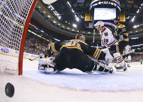The winning goal by Brent Seabrook, not shown, crosses into the net behind Boston Bruins goalie Tuukka Rask (40), of Finland, as Chicago Blackhawks center Jonathan Toews (19) and Boston Bruins defenseman Zdeno Chara (33), of Slovakia hover in front during the first overtime period in Game 4 of the NHL hockey Stanley Cup Finals, Wednesday, June 19, 2013, in Boston. Chicago won 6-5.  Chicago won 6-5. (AP Photo/Harry How, Pool)