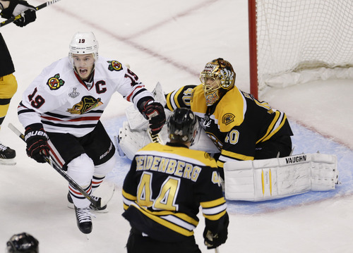 Chicago Blackhawks center Jonathan Toews (19) celebrates the winning goal by Brent Seabrook, not shown, against Boston Bruins goalie Tuukka Rask (40), of Finland, during the first overtime period in Game 4 of the NHL hockey Stanley Cup Finals, Wednesday, June 19, 2013, in Boston. (AP Photo/Charles Krupa)