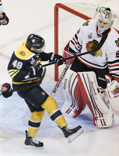 Boston Bruins center Rich Peverley (49) celebrates his goal in front of Chicago Blackhawks goalie Corey Crawford (50) during the first period in Game 4 of the NHL hockey Stanley Cup Finals, Wednesday, June 19, 2013, in Boston. (AP Photo/Charles Krupa)