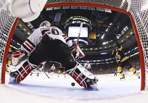 Boston Bruins left wing Daniel Paille, right, celebrates a goal past Chicago Blackhawks goalie Corey Crawford (50) by Boston Bruins center Rich Peverley, not seen, during the first period in Game 4 of the NHL hockey Stanley Cup Finals Wednesday, June 19, 2013, in Boston. (AP Photo/Harry How, Pool)