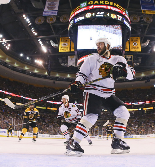 Chicago Blackhawks defenseman Brent Seabrook (7) and Chicago Blackhawks center Jonathan Toews (19) defend against the Boston Bruins during the first period in Game 4 of the NHL hockey Stanley Cup Finals Wednesday, June 19, 2013, in Boston. (AP Photo/Harry How, Pool)