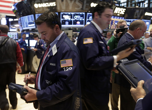 In this Monday, June 10, 2013 photo, Michael Iozzi, left, works with fellow traders on the floor of the New York Stock Exchange. World stock markets fell sharply Thursday June 20, 2013 after the U.S. Federal Reserve said it could start scaling back its huge economic stimulus program later this year and a survey showed  a slowdown in manufacturing in China. (AP Photo/Richard Drew)