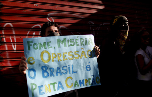 """A protester holds a sign that reads in Portuguese """"Hunger, misery and oppression and Brazil five time champions,"""" a few miles from the soccer stadium where Nigeria and Uruguay will play in a Confederations Cup soccer game in Salvador, Brazil, Thursday, June 20, 2013. Beginning as protests against bus fare hikes, demonstrations have quickly ballooned to include broad middle-class outrage over the failure of governments to provide basic services and ensure public safety. (AP Photo/Natacha Pisarenko)"""