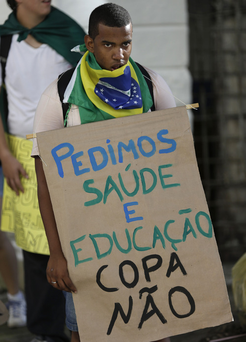 """A protester holds a banner that reads in Portuguese """"We ask for heath and education, not the cup,"""" referring to the Confederations Cup soccer tournament, a few miles from the soccer stadium where Nigeria and Uruguay will meet in Salvador, Brazil, Thursday, June 20, 2013. Beginning as protests against bus fare hikes, demonstrations have quickly ballooned to include broad middle-class outrage over the failure of governments to provide basic services and ensure public safety. (AP Photo/Natacha Pisarenko)"""