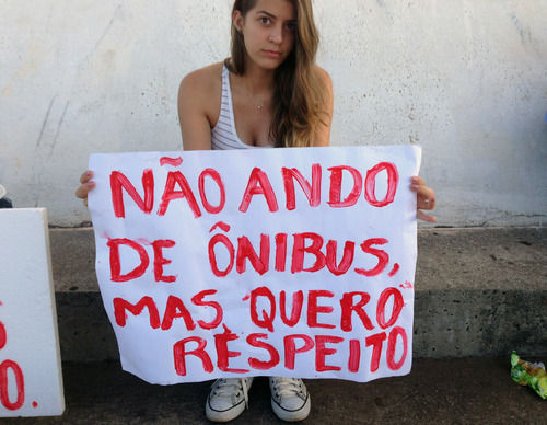 """Lorena Dias poses for a photo holding a sign that reads in Portuguese; """"I don't ride the bus, but I want respect,"""" at an anti-government protest, in Brasilia, Brazil, Thursday, June 20, 2013.  The 15-year-old student says, """"This is the time to change so much that is wrong in Brazil and it's young people who are leading the way. I see a sign of hope in this movement.""""(AP Photo/Marco Sibaja)"""