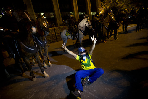A demonstrator flashes victory signs at police during an anti-government protest in Rio de Janeiro, Brazil, Thursday, June 20, 2013.  More than half a million poured into the streets of at least 80 Brazilian cities Thursday in demonstrations that saw violent clashes and renewed calls for an end to government corruption and demands for better public services. Riot police battled protesters in at least five cities, with some of the most intense clashes happening in Rio de Janeiro, where an estimated 300,000 demonstrators swarmed into the seaside city's central area. (AP Photo/Silvia Izquierdo)