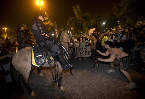Demonstrators confront Brazilian police on horseback during a protest in Rio de Janeiro, Brazil, Thursday, June 20, 2013.  Protests are planned in more than 80 cities across Brazil Thursday, a week after the start of massive demonstrations that have sent hundreds of thousands of people into the streets denouncing poor public services and government corruption.  Riot police battled protesters in at least five cities, with some of the most intense clashes happening in Rio de Janeiro, where an estimated 300,000 demonstrators swarmed into the seaside city's central area. (AP Photo/Silvia Izquierdo)