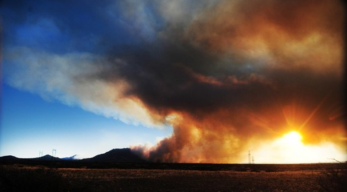In this Tuesday, June 18, 2013 photo, smoke shrouds the sunset late in the afternoon as the Doce Fire burns around the Northeast edge of Granite Mountain near Prescott, Ariz. The wildfire that has burned nearly 8 square miles just west of Prescott had moved into people's backyards Wednesday and has forced the evacuation of 460 homes. (AP Photo/The Daily Courier, Les Stukenberg) MANDATORY CREDIT