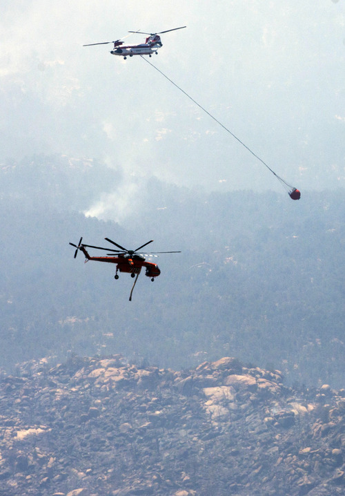 An Erickson Air-Crane and a Chinook pass each other  while fighting the Doce Fire near Prescott, Ariz., Wednesday, June 19, 2013. The wildfire that has burned nearly 8 square miles just west of Prescott had moved into people's backyards and has forced the evacuation of 460 homes. (AP Photo/The Arizona Republic, Pat Shannahan)  MARICOPA COUNTY OUT; MAGS OUT; NO SALES