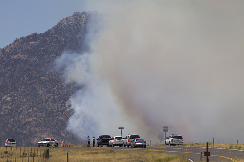 A police road block prevents traffic from traveling near the Doce Fire as it burns towards homes on Wednesday, June 19, 2013 in the hills northwest of Prescott, Ariz. The wildfire that has burned nearly 8 square miles just west of Prescott had moved into people's backyards and has forced the evacuation of 460 homes. (AP Photo/The Arizona Republic, Rob Schumacher)  MARICOPA COUNTY OUT; MAGS OUT; NO SALES