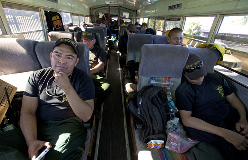 Crew boss Neil Damon (left) with the Navajo Scouts, a Type II hotshot team from Fort Defiance, AZ, rest on their bus before working a night shift tonight at the Doce Fire on Wednesday, June 19, 2013 in the hills northwest of Prescott, AZ. The fire has burned 7,000 acres and 460 homes have been evacuated. (AP Photo/The Arizona Republic, Rob Schumacher)