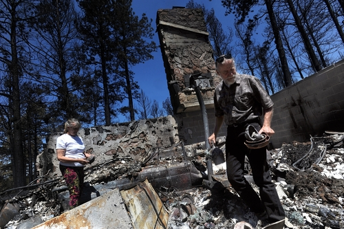 Eric Olson and his wife, Bonnie Olson, sort through their belongings Wednesday, June 19, 2013, while visiting their destroyed home on Shoup Road in Black Forest north of Colorado Springs, Colo.  (AP Photo/The Gazette, Christian Murdock)