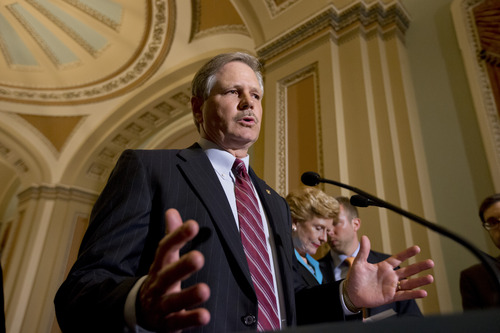 In this photo taken June 10, 2013, Sen. John Hoeven, R-N.D., speaks to reporters as the Senate votes on a farm bill, on Capitol Hill in Washington. Hoeven and Sen. Bob Corker, R-Tenn., are pushing an amendment on the current immigration bill that would strengthen border security. (AP Photo/J. Scott Applewhite)