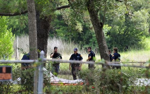 Jacksonville Fire Rescue personnel gather near a creek behind homes on Villanova Road off Broward Road in Jacksonville, Fla. on Saturday, June 22, 2013. Authorities said the body of 8-year-old Charish Perriwinkle was found in the area. An Amber Alert was issued after she went missing Friday night, but authorities began a murder investigation after her body was found. (AP Photo/The Florida Times-Union, Will Dickey)