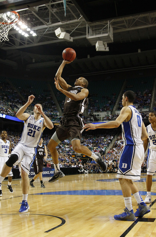 Lehigh's C.J. McCollum shoots as Duke's Miles Plumlee (21) and Austin Rivers (0) defend during the second half of a South Regional NCAA tournament second-round college basketball game in Greensboro, N.C., Friday, March 16, 2012. Lehigh won 75-70. (AP Photo/Gerry Broome)