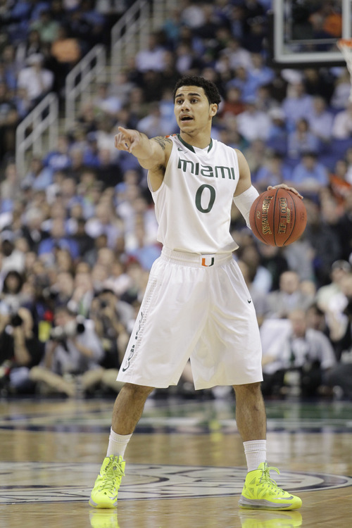 Miami's Shane Larkin (0) directs the team against North Carolina during the first half of an NCAA college basketball game in the championship of the Atlantic Coast Conference tournament in Greensboro, N.C., Sunday, March 17, 2013. (AP Photo/Bob Leverone)