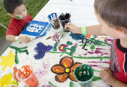 Keith Johnson  |  The Salt Lake Tribune Zedriak Montero, 4, and Bryce Sellers, 7, paint at one of the craft tables during World Refugee Day at Liberty Park in Salt Lake City, June 22, 2013.