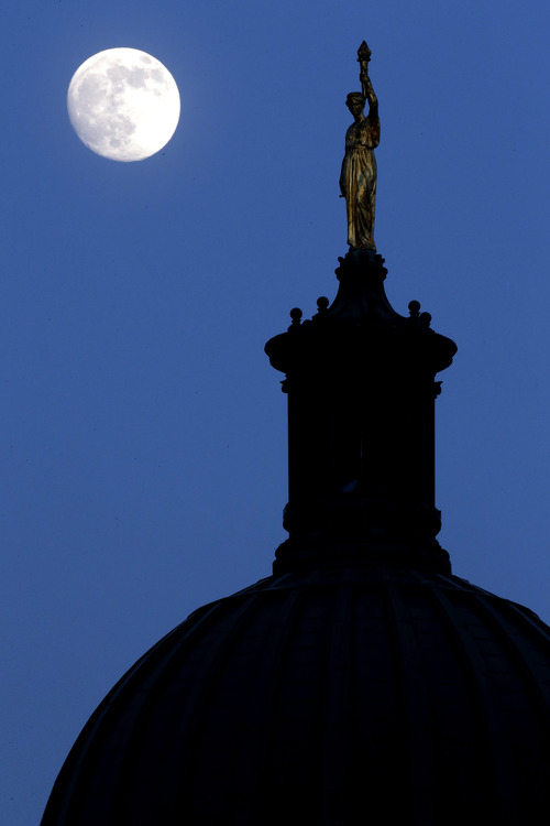 """The moon in its waxing gibbous stage is shines behind a statue entitled """"Enlightenment Giving Power"""" by John Gelert, which sits at the top of the dome of the Bergen County Courthouse in Hackensack, N.J., Friday, June 21, 2013. The moon, which will reach its full stage on Sunday, is expected to be 13.5 percent closer to earth during a phenomenon known as supermoon. (AP Photo/Julio Cortez)"""
