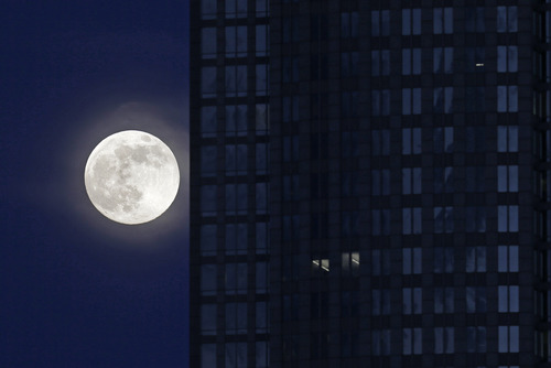 """A full moon rises beside an office building in downtown Charlotte, N.C., Saturday, June 22, 2013. The larger than normal moon called the """"Supermoon"""" happens only once this year as the moon on its elliptical orbit is at its closest point to earth.(AP Photo/Chuck Burton)"""