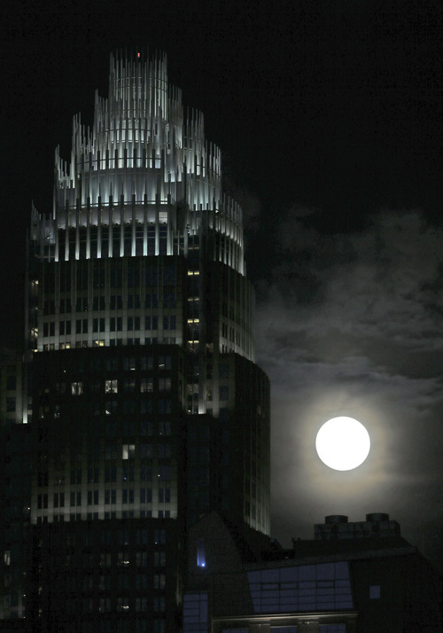 """A full moon rises beside the Bank of America corporate headquarters in downtown Charlotte, N.C., Saturday, June 22, 2013. The larger than normal moon called the """"Supermoon"""" happens only once this year as the moon on its elliptical orbit is at its closest point to earth.(AP Photo/Chuck Burton)"""