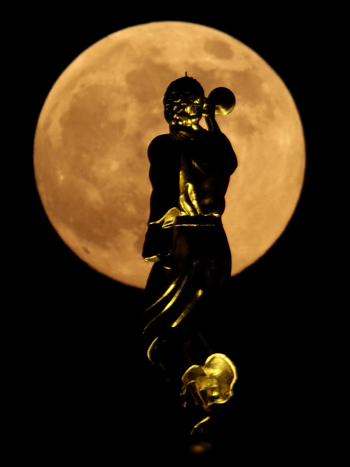 A statue of the Angel Moroni on top a Latter-day Saints temple is silhouetted against the rising moon Saturday, June 22, 2013, in Kansas City, Mo. The moon, which will reach its full stage on Sunday, is expected to be 13.5 percent closer to earth during a phenomenon known as supermoon. (AP Photo/Charlie Riedel)