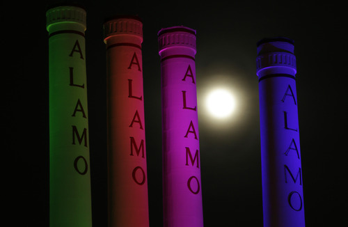 """A hazy """"supermoon"""" is seen behind lighted smoke stacks at the Alamo Quarry Markey, formerly a cement factory, Saturday, June 22, 2013, in San Antonio. The biggest and brightest full moon of the year graces the sky early Sunday as our celestial neighbor swings closer to Earth than usual. While the moon will appear larger than normal, sky watchers won't be able to notice the difference with the naked eye.(AP Photo/Eric Gay)"""
