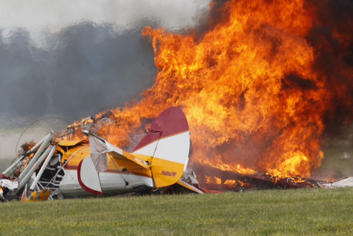 Flames erupt from a plane after it crashed at the Vectren Air Show at the airport in Dayton, Ohio. The crash killed the pilot and stunt walker on the plane instantly, authorities said. (AP Photo/Dayton Daily News, Ty Greenlees)