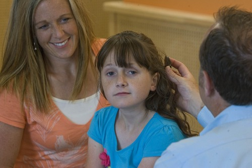 Paul Fraughton  |   Salt Lake Tribune As her mother Jill Heaps looks on,   Cache Pitt, a doctor of audiology,  helps  Emily Heaps, age 11 with the exterior portion of   her cochlear implants. Hearing loss was  as a residual effect from Emily's  SCID, otherwise known as Boy in the Bubble Syndrome. Two bone marrow transplants have cured her of the  disease.                          Monday, June 17, 2013
