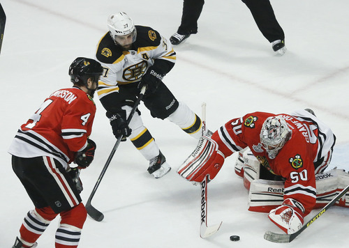 Boston Bruins center Patrice Bergeron (37) looks to score against Chicago Blackhawks goalie Corey Crawford (50) in the first period during Game 5 of the NHL hockey Stanley Cup Finals, Saturday, June 22, 2013, in Chicago. Bergeron left the game with an injury in the second period and did not return. (AP Photo/Nam Y. Huh)